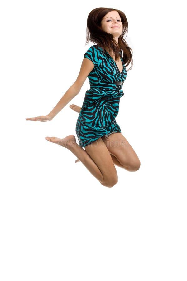 Mulher nova que salta altamente no ar com um SMI grande imagens de stock royalty free