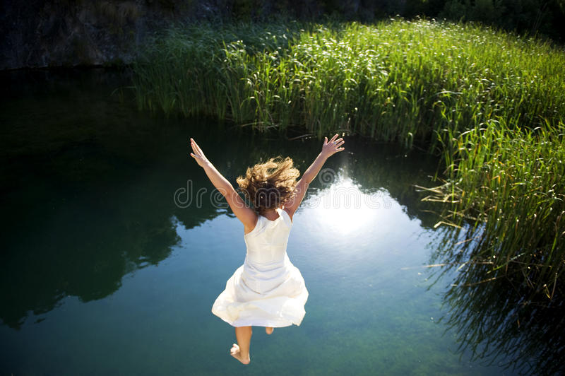 Mulher nova que salta na água fotos de stock royalty free