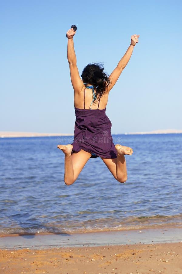 Mulher nova que salta na praia imagens de stock