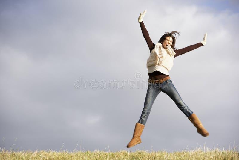 Mulher nova que salta no ar fotos de stock