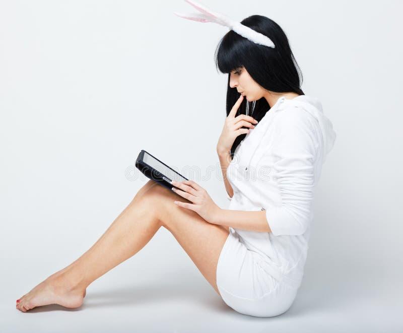 Mulher nova que senta-se com PC da tabuleta imagem de stock