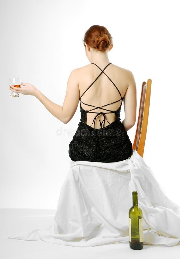 Mulher nova que senta-se com wineglass, vista traseira imagens de stock royalty free