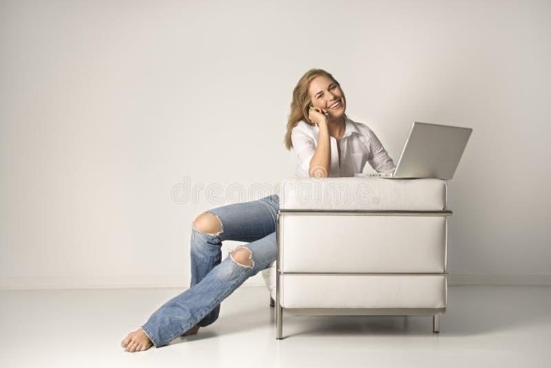 Mulher nova que senta-se na cadeira com um portátil e um Cel foto de stock