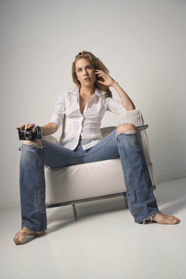 Mulher nova que senta-se na cadeira e que prende a câmera fotografia de stock royalty free