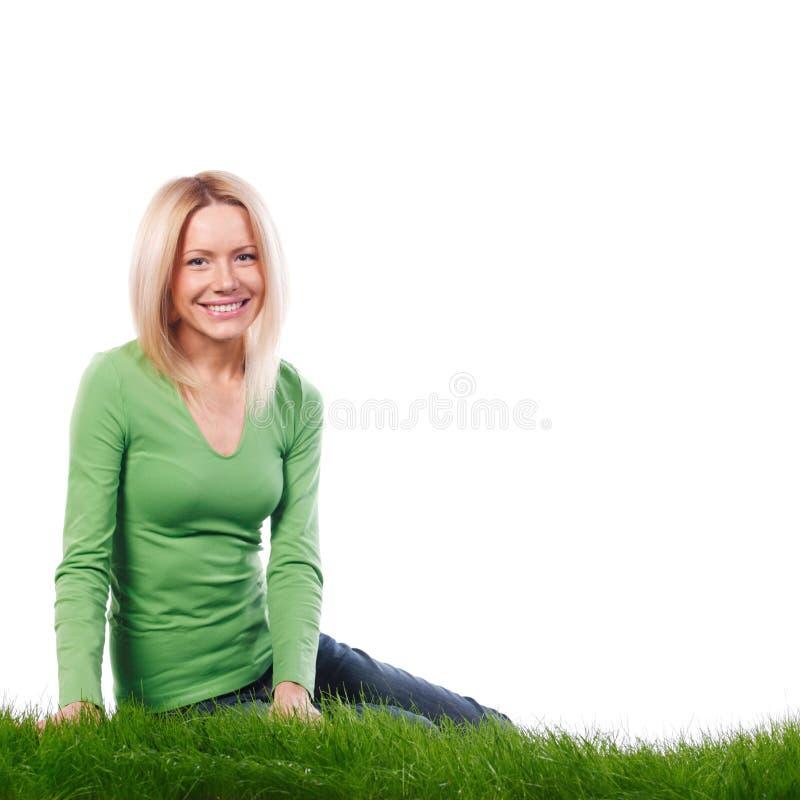 Mulher nova que senta-se na grama foto de stock