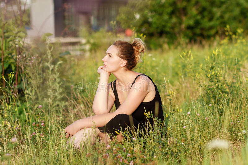 Mulher nova que senta-se na grama imagens de stock