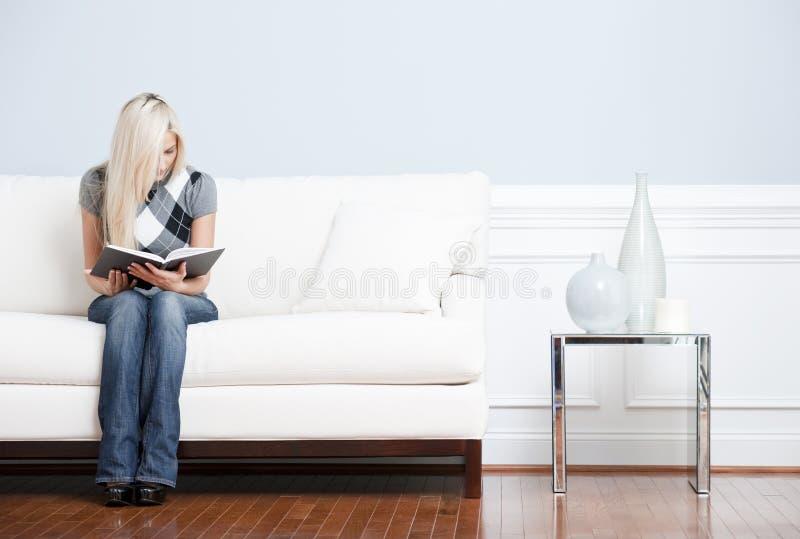 Mulher nova que senta-se na leitura do sofá imagem de stock