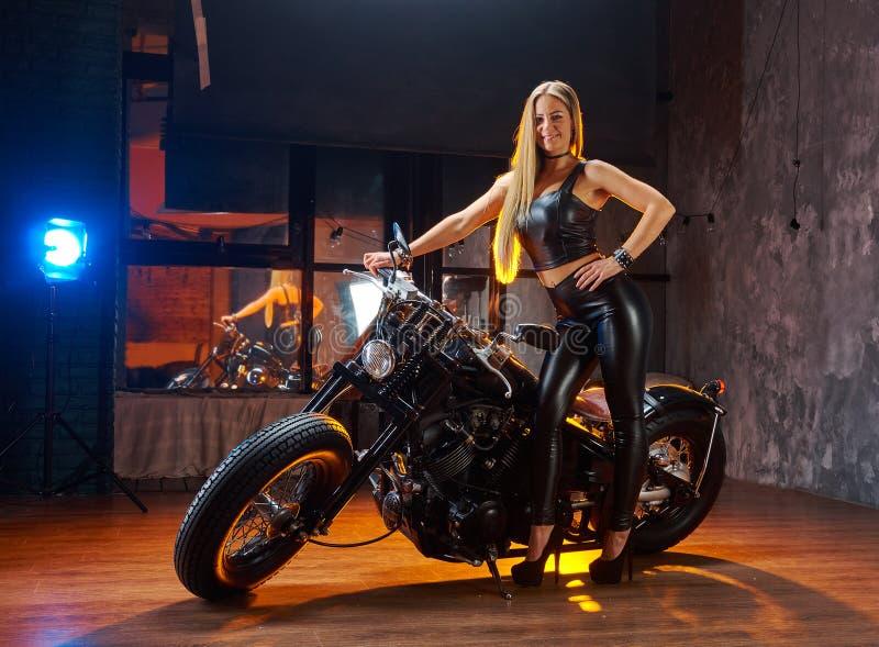 Mulher nova que senta-se na motocicleta imagem de stock
