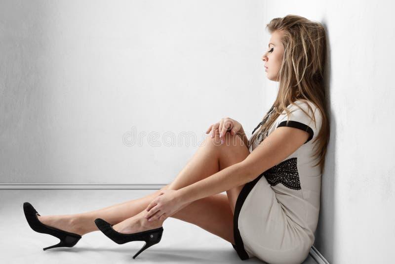 Mulher nova que senta-se no assoalho foto de stock