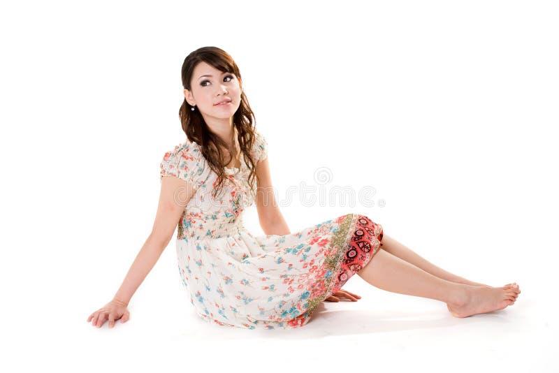 Mulher nova que senta-se no flo fotografia de stock