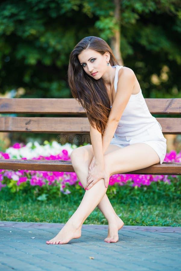 Mulher nova que senta-se no parque fotografia de stock