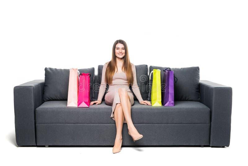 Mulher nova que senta-se no sofá que compra em linha com sacos de compra imagem de stock