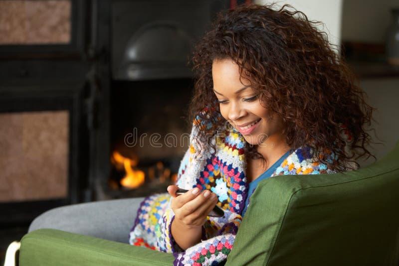 Mulher nova que senta-se pelo incêndio com telefone imagens de stock