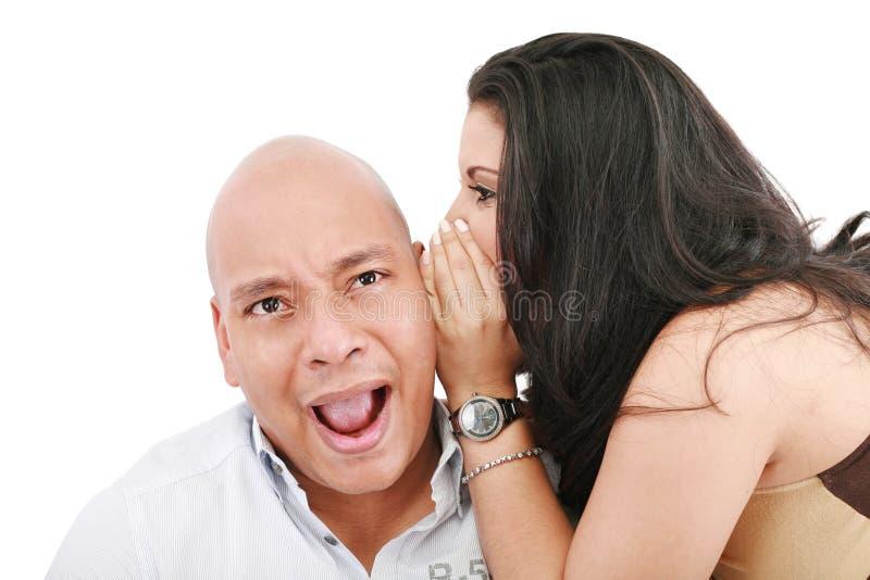 Mulher nova que sussurra em sua orelha do marido fotos de stock