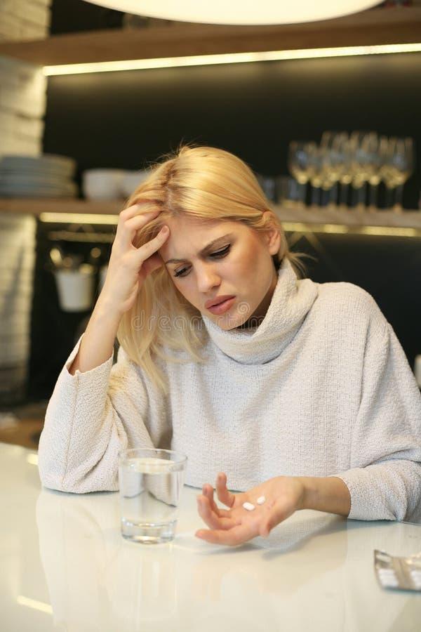 Mulher nova que tem a dor de cabeça imagens de stock