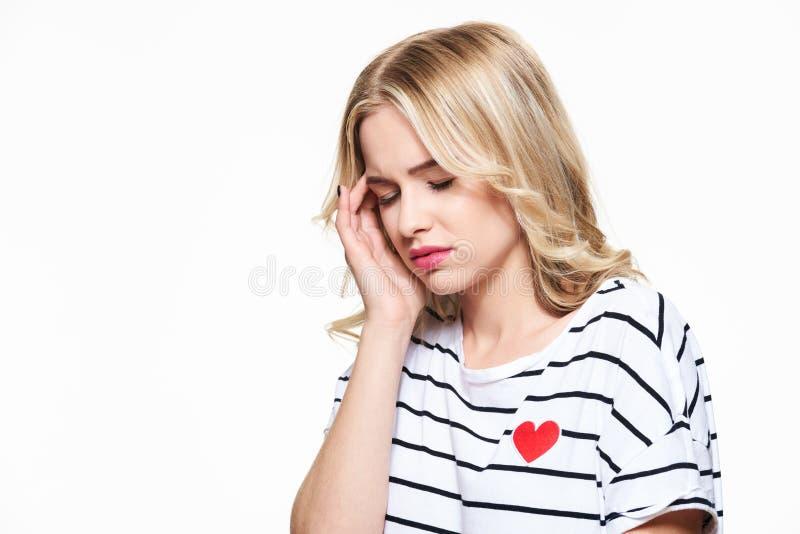 Mulher nova que tem a dor de cabeça Jovem mulher esgotada forçada que tem a dor de cabeça de tensão forte Sofrimento da enxaqueca fotografia de stock royalty free