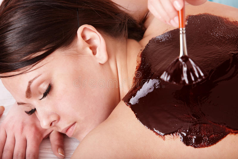 Mulher nova que tem a máscara do bodyl do chocolate. imagens de stock royalty free