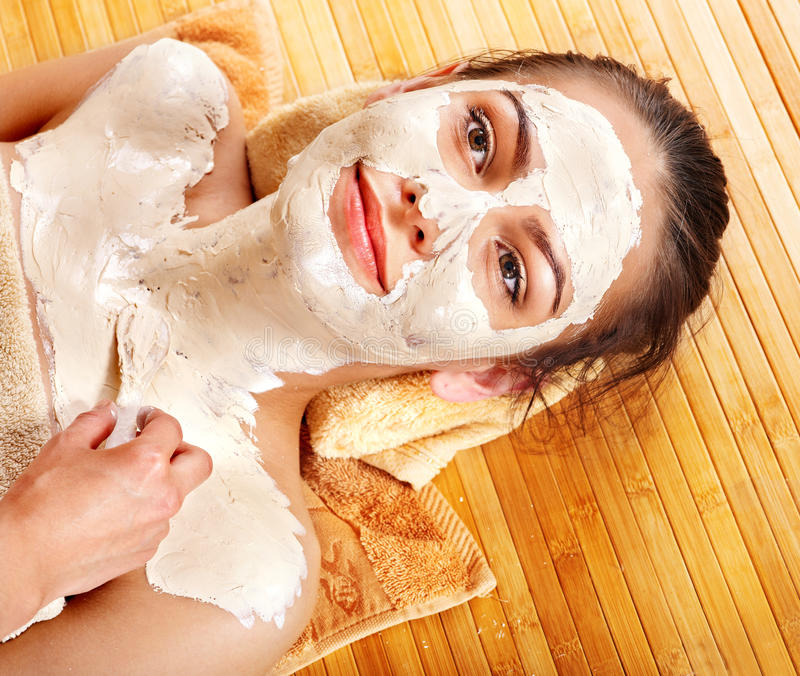 Mulher nova que tem a máscara do facial da argila. imagem de stock