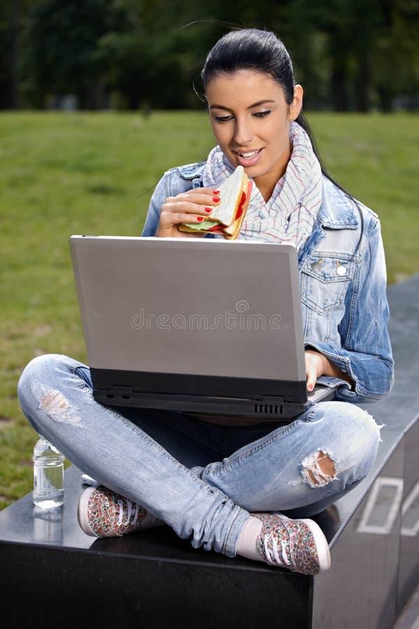 Mulher nova que tem o almoço no parque usando o portátil imagem de stock
