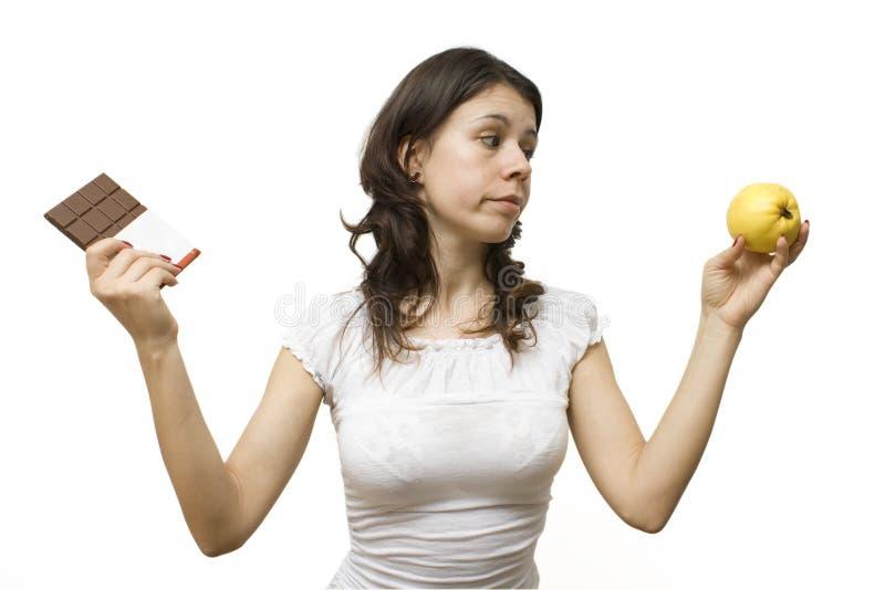 Mulher nova que tem um dilema do alimento imagens de stock