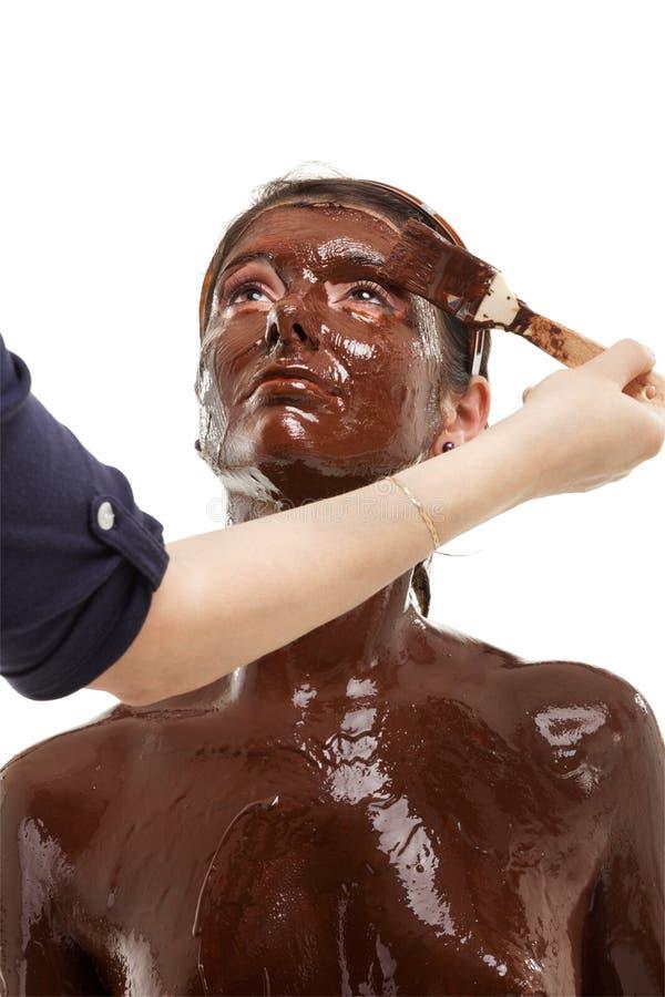 Mulher nova que tem uma máscara protectora do chocolate imagens de stock royalty free