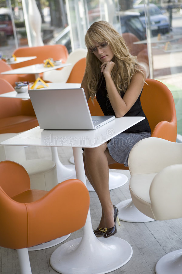 Mulher nova que trabalha com computador em um café foto de stock royalty free