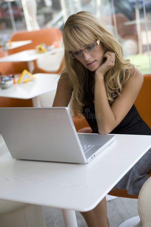 Mulher nova que trabalha com um portátil em um café foto de stock royalty free