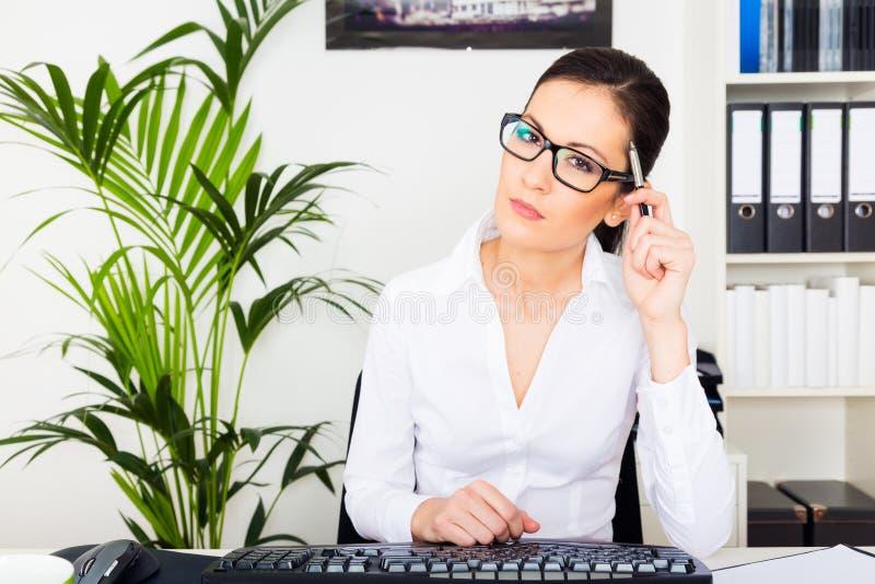 Mulher nova que trabalha em seu computador imagens de stock