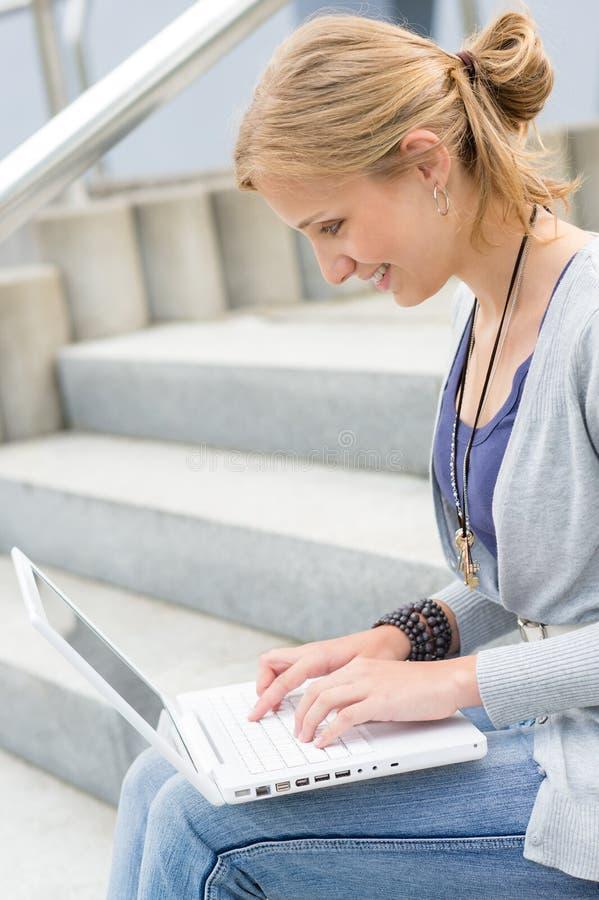 Mulher nova que trabalha em seu computador portátil fotografia de stock
