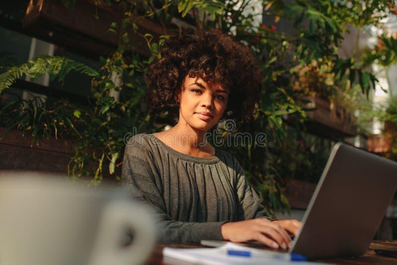 Mulher nova que trabalha no portátil imagem de stock