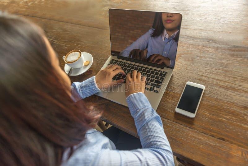 Mulher nova que trabalha no portátil foto de stock