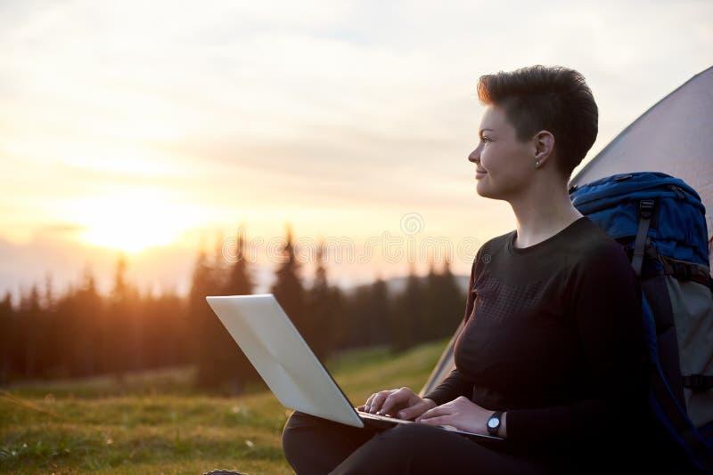 Mulher nova que usa o portátil ao ar livre imagem de stock