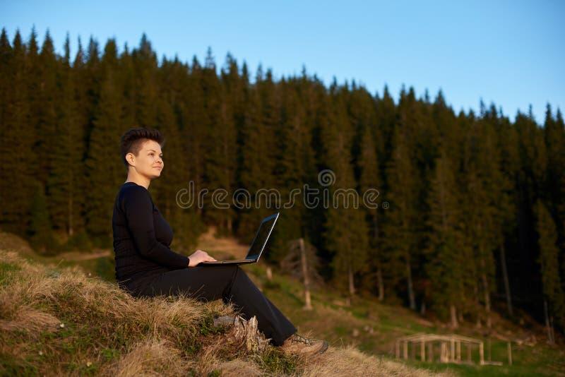 Mulher nova que usa o portátil ao ar livre fotografia de stock royalty free