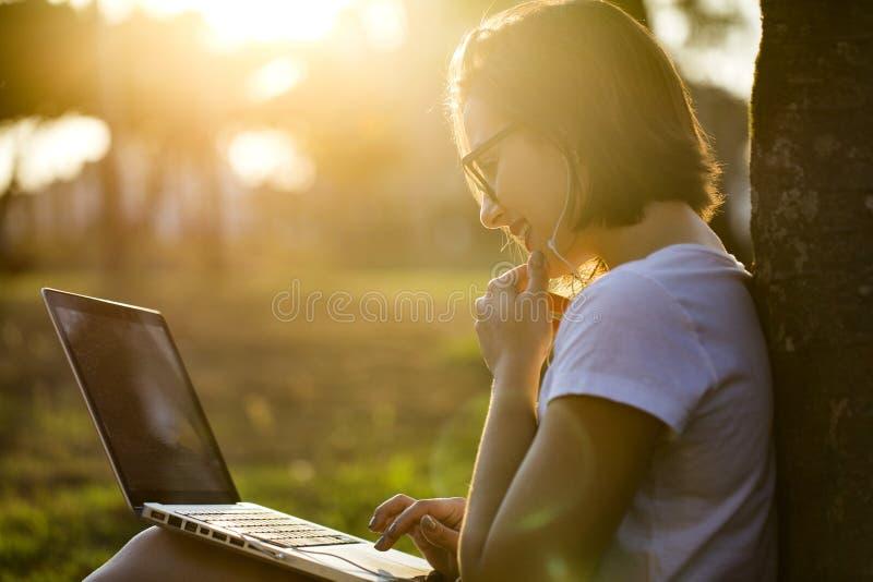 Mulher nova que usa o portátil no parque fotos de stock royalty free