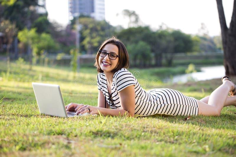 Mulher nova que usa o portátil no parque imagens de stock