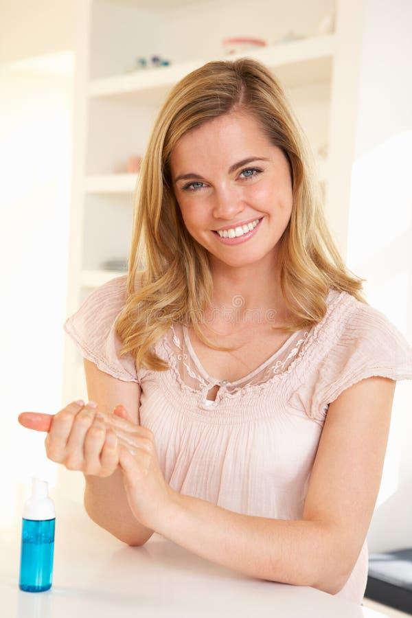 Mulher nova que usa o sanitizer da mão foto de stock royalty free