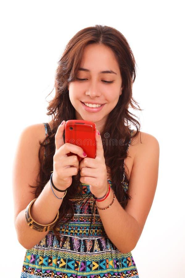Mulher nova que usa um telefone de pilha imagem de stock