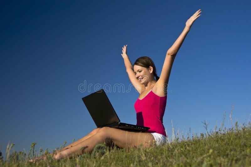 Mulher nova que usam um portátil, e feliz bonitos. fotografia de stock