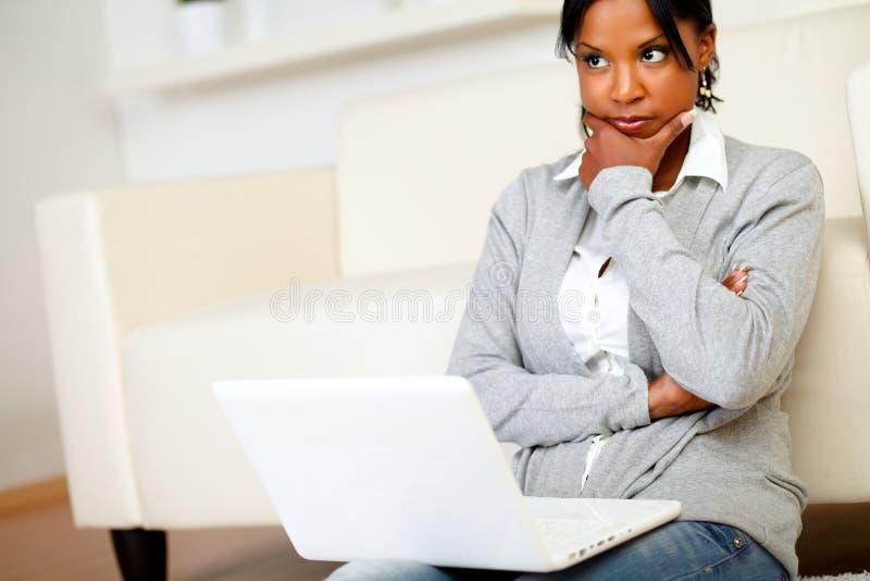 A mulher nova reflexiva senta-se no assoalho imagem de stock royalty free