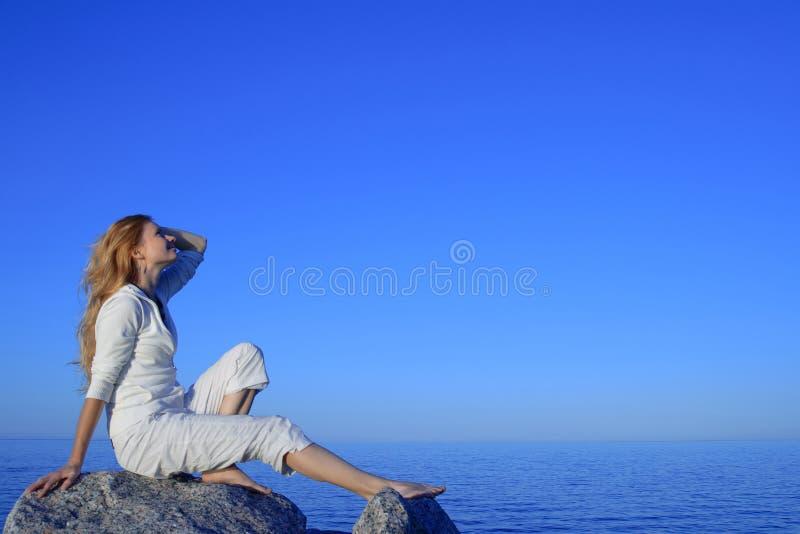 Mulher nova Relaxed que aprecia o por do sol pelo mar fotos de stock