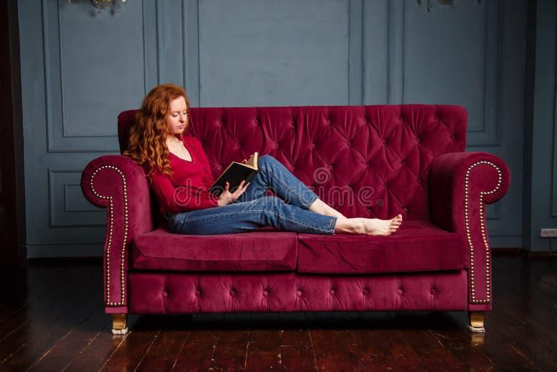 Mulher nova rica do ruivo que lê um livro no sofá vermelho de veludo imagem de stock