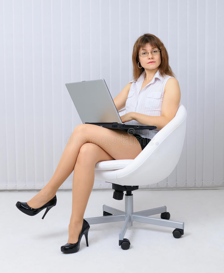 Mulher nova séria, bonita que senta-se em uma cadeira fotos de stock
