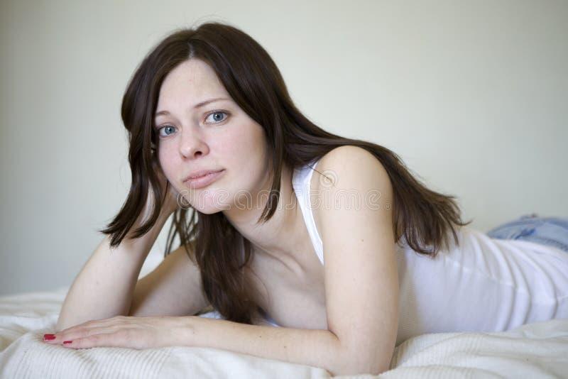 Mulher nova séria que encontra-se no assoalho de madeira imagem de stock