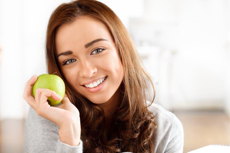 Mulher nova saudável que prende a maçã verde imagem de stock