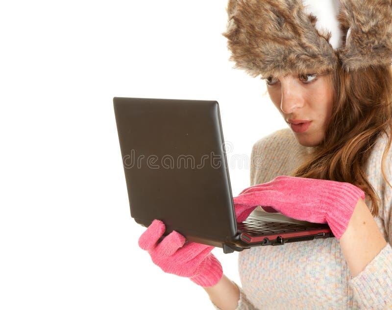 Mulher nova Scared do inverno que usa o portátil foto de stock