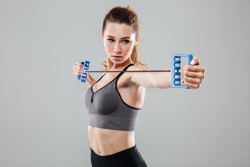 Mulher nova segura da aptidão que faz exercícios com expansor fotos de stock