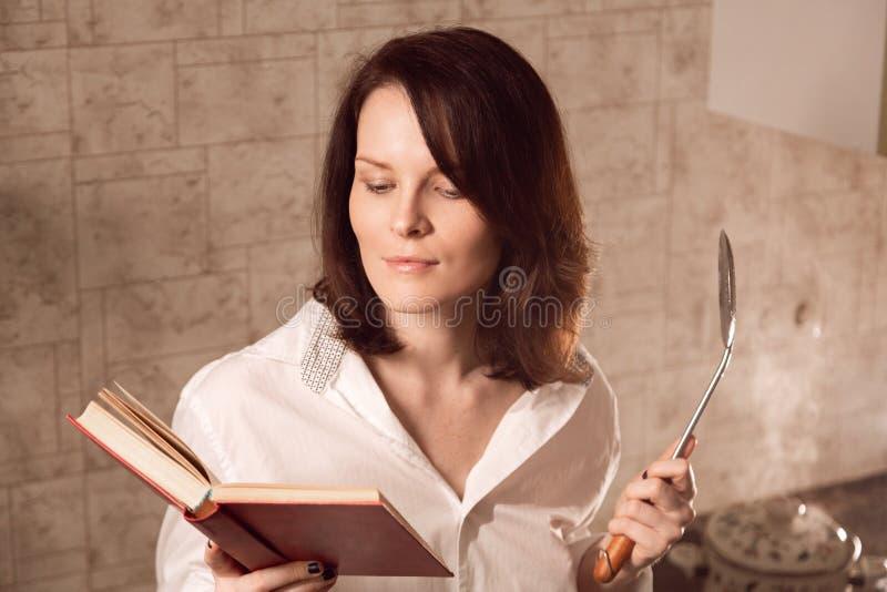 Mulher nova sensual do ruivo que lê um livro ao cozinhar na cozinha foto de stock