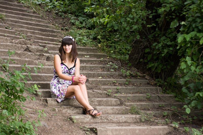 A mulher nova senta no escadas foto de stock