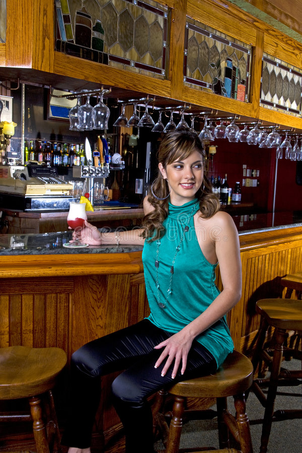 A mulher nova senta-se em uma barra fotografia de stock