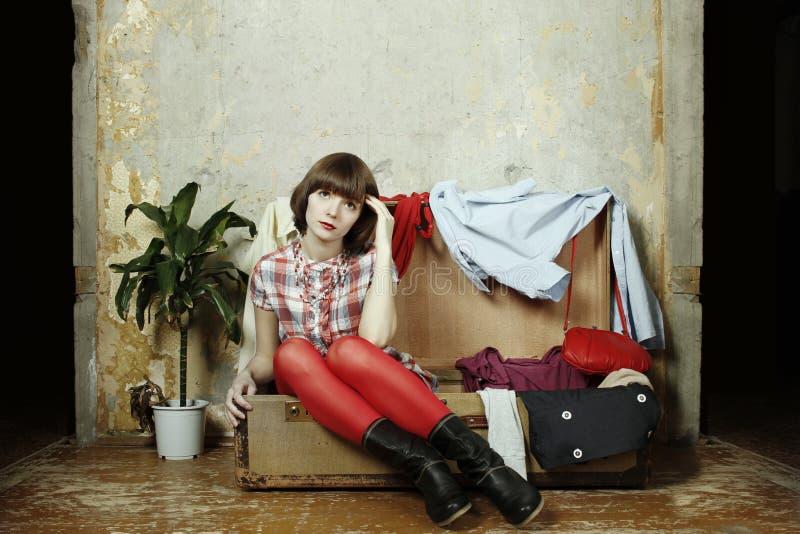 A mulher nova senta-se em uma mala de viagem enchida com a roupa fotos de stock royalty free
